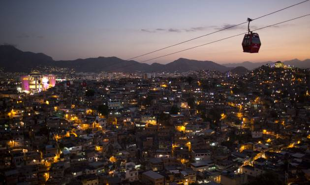 In this May 10, 2013 photo, homes are lit at night as cable-cars move commuters over the Complexo do Alemao complex of shantytowns in Rio de Janeiro, Brazil.  The cable-car system linking six of its hilltops over a 3.5-kilometer (2.3-mile) route has become a popular tourist attraction. (AP Photo/Felipe Dana)