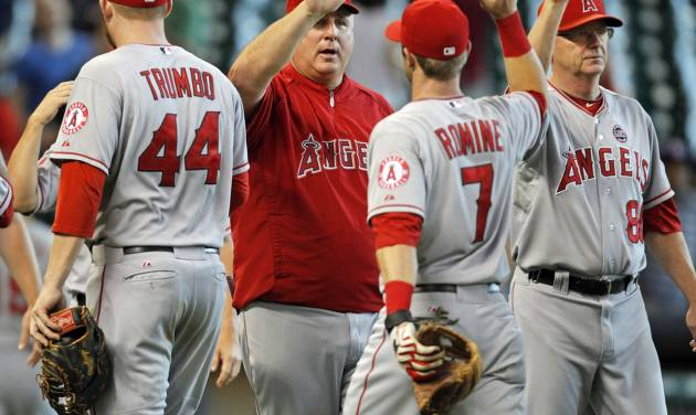 Los Angeles Angels manager Mike Scioscia, center, celebrates Andrew Romine (7) after the Angels 2-1 victory over the Houston Astros in a baseball game Sunday, Sept. 15, 2013, at Minute Maid Park in Houston. (AP Photo/Eric Christian Smith)