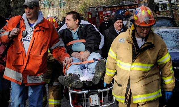 "FILE - In this Dec. 1, 2013 photo, Metro North Railroad engineer William Rockefeller is wheeled on a stretcher away from the area where the commuter train he was operating derailed, killing four people, in the Bronx borough of New York. The deadly derailment last year, in which the ""dazed"" engineer was found to have sleep apnea, has pushed the commuter railroad to look into establishing screening for the condition, which could include measuring operators' necks and asking them and their spouses about snoring habits. A Metro-North spokesman confirmed the railroad that serves New York City's northern suburbs is working with unions on sleep apnea screening, but he cautioned nothing has been decided.(AP Photo/Robert Stolarik, File)"