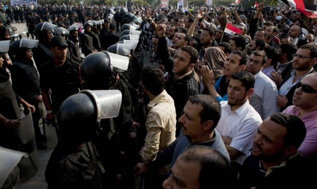 """Supporters of Egyptian President Mohammed Morsi chant slogans as riot police, left, stand guard in front of the entrance of Egypt's top court, in Cairo, Egypt, Sunday, Dec. 2, 2012. Egypt's top court announced on Sunday the suspension of its work indefinitely to protest """"psychological and physical pressures,"""" saying its judges could not enter its Nile-side building because of the Islamist president's supporters gathered outside. (AP Photo/Nasser Nasser)"""