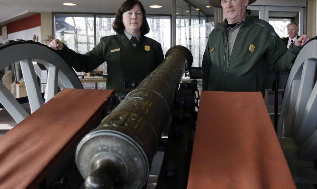 "Saratoga National Historical Park Curator Christine Valosin, left, and superintendent Joe Finan pose with a Revolutionary War cannon after a ceremony for the cannon at the park on Friday, Nov. 15, 2013, in Stillwater, N.Y. The cannon surrendered by the British after the Battles at Saratoga is back ""home"" after stints in museums and private collections in four states over the past half-century. Officials at Saratoga say the rare Revolutionary War cannon was tracked down to Alabama's Tuscaloosa Museum of Art and recently delivered to the park, located 20 miles north of Albany. (AP Photo/Mike Groll)"
