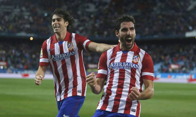 Atletico's Raul Garcia, centre, celebrates his goal with Tiago during a Spanish Copa del Rey soccer match between Atletico de Madrid and Valencia at the Vicente Calderon stadium in Madrid, Spain, Tuesday, Jan. 14, 2014. (AP Photo/Andres Kudacki)