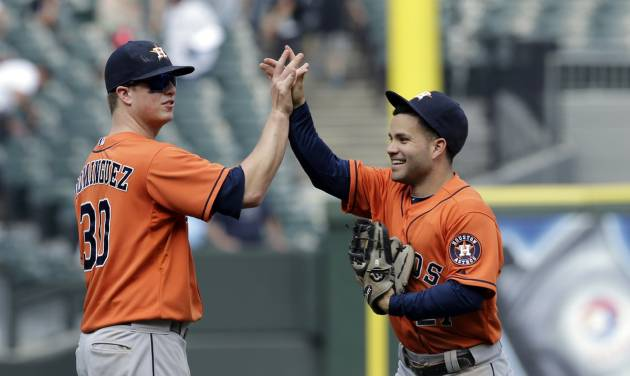 Houston Astros' Matt Dominguez, left, celebrates with Jose Altuve after the Astros defeated the Chicago White Sox 11-7 in a baseball game in Chicago on Sunday, July 20, 2014. (AP Photo/Nam Y. Huh)