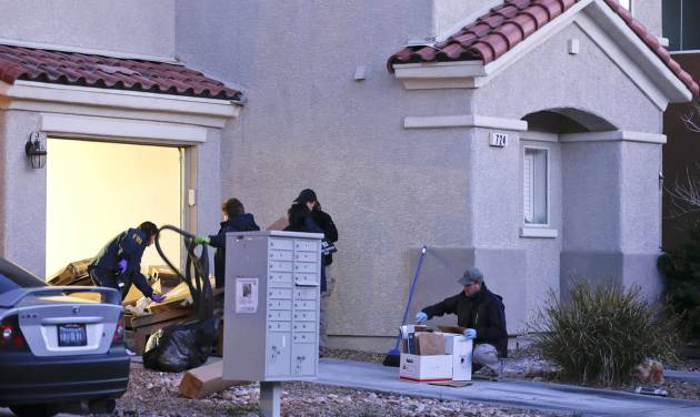 """FBI agents gather outside a Las Vegas home owned by former Los Angeles police officer Christopher Dorner while collecting evidence, Thursday, Feb. 7, 2013. Thousands of police officers hunted Thursday for one of their own: a former Los Angeles officer angry over his firing and sought in a deadly shooting rampage after warning he would wage """"warfare"""" on those who wronged him, authorities said. (AP Photo/Julie Jacobson)"""
