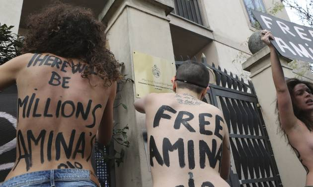FILE - In this April 4, 2013 file photo, FEMEN activists protest in front of the Tunisian Consulate in Milan, Thursday, April 4, 2013. The radical feminists, calling for more sexual freedom for Arab women, were protesting in support of a young Tunisian woman who received online death threats from ultraconservative Muslims after posting topless photos of herself online. Women's rights activists across the middle east fear the topless protests may hurt their cause more than help it. (AP Photo/Antonio Calanni)