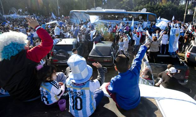 Fans of Argentina's national soccer team wave to the bus taking the players to the airport in Buenos Aires, Argentina, Monday, June 9, 2014. Argentina's team is leaving Monday to compete in the Brazil's 2014 soccer Word Cup. (AP Photo/Natacha Pisarenko)