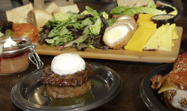 Sticky Toffee pudding, front center, is displayed along with the Ploughman's Platter, back, available at the Leaky Cauldron restaurant during a preview of Diagon Alley at the Wizarding World of Harry Potter at Universal Orlando, Thursday, June 19, 2014, in Orlando, Fla. (AP Photo/John Raoux)
