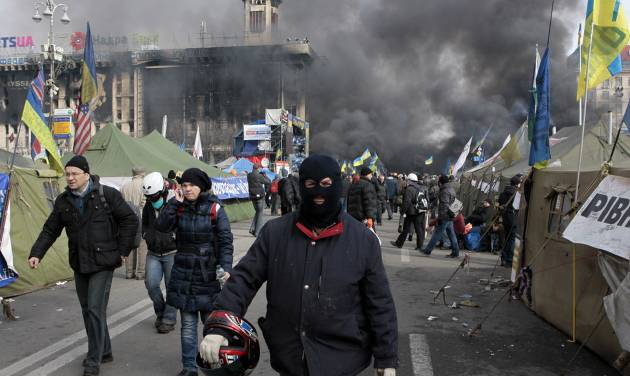 An anti-government protester walks away during clashes with riot police in Kiev's Independence Square, the epicenter of the country's current unrest, Kiev, Ukraine, Wednesday, Feb. 19, 2014. The deadly clashes in Ukraine's capital have drawn sharp reactions from Washington, generated talk of possible European Union sanctions and led to a Kremlin statement blaming Europe and the West.  (AP Photo/Sergei Chuzavkov)