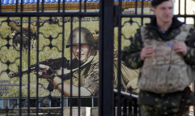 A Ukrainian soldier stands guard at the gate of a military base in the port of Kerch, Ukraine, Monday, March 3, 2014. Pro-Russian troops controlled a ferry terminal on the easternmost tip of Ukraine's Crimea region close to Russia on Monday, intensifying fears that Moscow will send even more troops into the strategic Black Sea region in its tense dispute with its Slavic neighbor. (AP Photo/Darko Vojinovic)