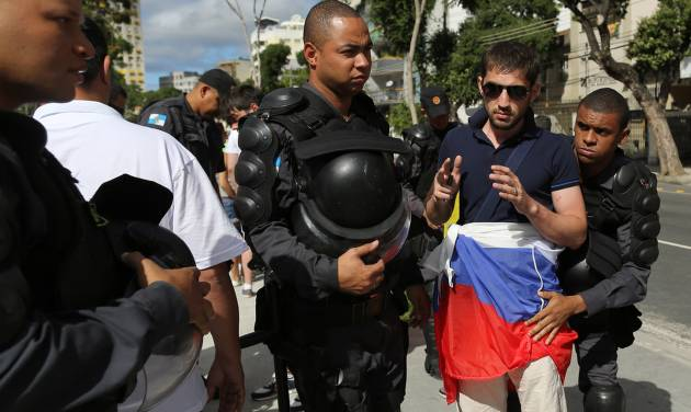 Riot policemen search a soccer fan wearing Russia's team colors as he arrives to Maracana stadium  for the group H World Cup match between Belgium and Russia, in Rio de Janeiro, Brazil, Sunday, June 22, 2014. (AP Photo/Leo Correa)
