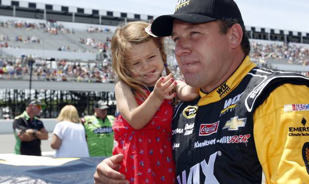 Driver Ryan Newman holds his daughter Brooklyn in the pits before the NASCAR Sprint Cup Series Pocono 400 auto race at Pocono Raceway on Sunday, June 8, 2014, in Long Pond, Pa. (AP Photo/Mike Groll)