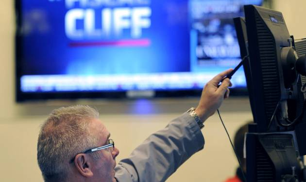 "FILE - In this Nov. 7, 2012, file photo, James Dresch of MND Partners Inc. works on the floor of the New York Stock Exchange in New York. Wall Street also appeared headed for gains on the open Wednesday Nov. 14, 2012 as renewed efforts got under way in Washington to resolve the impending ""fiscal cliff."" (AP Photo/Henny Ray Abrams, File)"