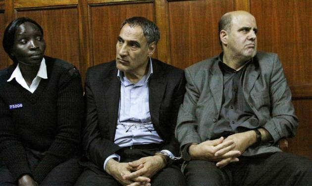 FILE - In this Wednesday, June 27, 2012 file photo, a Kenyan policewoman accompanies Iranian nationals Sayed Mansour Mousavi, center, and Ahmad Abolfathi Mohammad, right, in the Nairobi magistrates court in Nairobi, Kenya, where they faced charges related to the possession of explosives. On Monday, July 2, 2012, officials told The Associated Press that Mousavi and Mohammad, who led authorities to a cache of explosives after their arrest, planned to attack Israeli, U.S., British or Saudi targets inside Kenya. (AP Photo/Khalil Senosi, File)