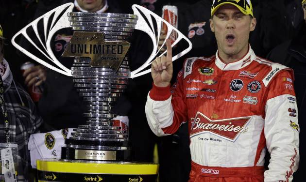 Kevin Harvick stands in Victory Lane next to the championship trophy after winning the NASCAR Sprint Unlimited auto race at Daytona International Speedway, Saturday, Feb. 16, 2013, in Daytona Beach, Fla.(AP Photo/John Raoux)