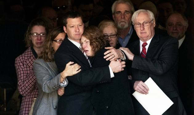 In this Nov. 9, 2012 photo, Jason Derkosh holds his wife, Elizabeth, at the funeral of their 2-year-old son, Maddox, at Saint Bernard Church in Mount Lebanon, Pa. The Pittsburgh Zoo & PPG Aquarium says Elizabeth Derkosh, the mother of 2-year-old  Maddox Derkosh, who was fatally mauled when he fell into a wild African dogs exhibit, is to blame for her son's death and shouldn't be allowed to sue. The zoo's attorneys made that argument in a response filed Monday Sept. 9, 2013 to the wrongful-death lawsuit brought by Jason and Elizabeth Derkosh.  Maddox Derkosh died Nov. 4, 2012 after falling over a 4-foot-tall wooden railing into the exhibit when his mother lifted him up to get a better look.(AP Photo/Tribune Review, Justin Merriman)  PITTSBURGH OUT