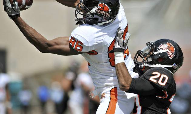 FILE - In this April 28, 2012, file photo, Oregon State receiver Obum Gwacham catches a pass while defended by cornerback Keynan Parker during a spring NCAA college football game in Corvallis, Ore. Gwacham wants one more chance to make his mark at Oregon State. Having struggled at wide receiver his entire college career, the 6-foot-5 senior is switching to defensive end. (AP Photo/The Corvallis Gazette-Times, Andy Cripe, File) MAGS OUT