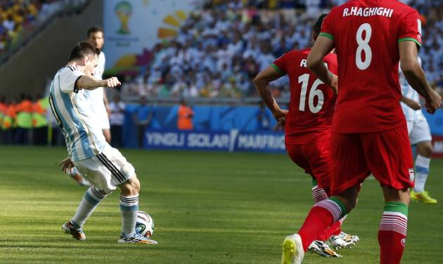 Argentina's Lionel Messi, left, scores during the group F World Cup soccer match between Argentina and Iran at the Mineirao Stadium in Belo Horizonte, Brazil, Saturday, June 21, 2014. Argentina won 1-0. (AP Photo/Jon Super)