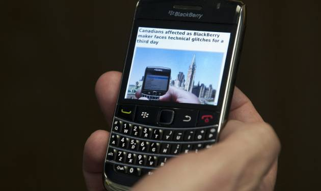 FILE - In this Oct. 12, 2011, file photo, A Blackberry subscriber holds a Research in Motion Blackberry in Ottawa. BlackBerry users will be able to make free voice calls over a Wi-Fi network using the popular BBM messaging service. Research In Motion Ltd. announced Wednesday that it's adding the feature to BBM. Users will be able to switch back and forth from a text chat to a(AP Photo/The Canadian Press, Adrian Wyld)