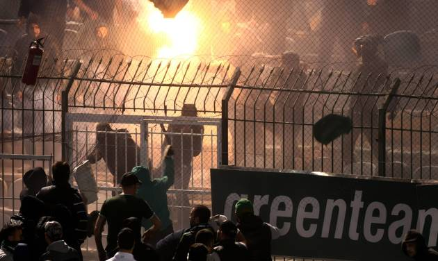 Panathinaikos and PAOK fans clash each other shortly before the start of the Greek championship play-off match between their teams at Apostolos Nikolaidis stadium in Athens, Sunday, May 4, 2014. (AP Photo/InTime Sports)  GREECE OUT