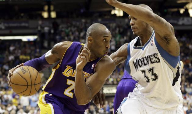 Los Angeles Lakers' Kobe Bryant, left, drives the basket on Minnesota Timberwolves' Dante Cunningham in the third quarter of an NBA basketball game Friday, Feb. 1, 2013 in Minneapolis.  Bryant scored 17 points and had 12 rebounds along with Pau Gasol as the Lakers won 111-100. (AP Photo/Jim Mone)