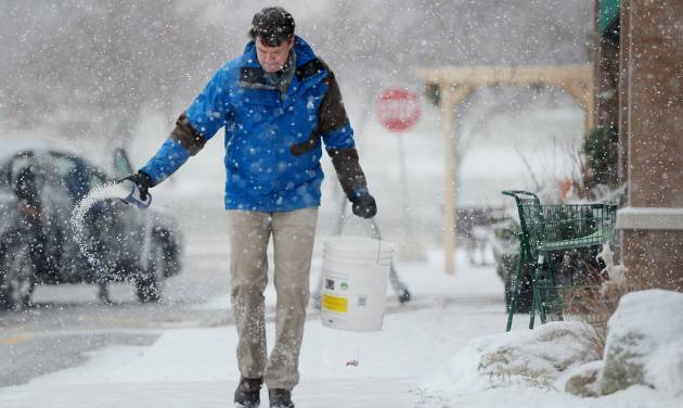 REI Assistant Store Manager Noel Seeburg salts the sidewalk after shoveling in front of the store located in the Cranbrook Village Shopping Center in Ann Arbor, Mich. on Wednesday, Dec. 26, 2012.  (AP Photo/AnnAbor.Com, Melanie Maxwell)