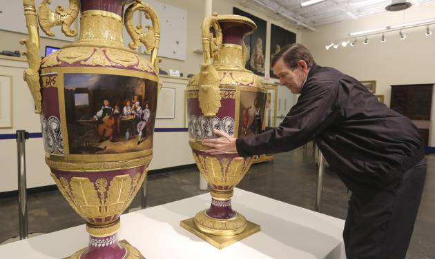 In this photo made Thursday, April 4, 2013, Jerry Holley, executive vice president of Dallas Auction Gallery, rotates a rare Russian vases made in 1833 by Russia's Imperial Porcelain Factory and on display at the gallery in Dallas. The rare 4 1/2-foot tall vases, which had been packs away for around a decade, were sold Thursday, April 11, 2013, for $2.7 million in a private sale about a week before they were to be auctioned. (AP Photo/LM Otero)