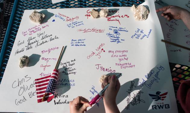 Active members of the military, veterans and civilians sign posters at Lions Club Park that will be delivered to the families of the victims affected by the Fort Hood shooting tragedy, on Friday, April 4, 2014, in Killeen, Texas. On April 2, three people were killed and 16 were wounded when a gunman opened fire before taking his own life at the Fort Hood military base. (AP Photo/Tamir Kalifa)