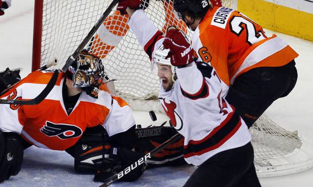 Philadelphia Flyers goalie Ilya Bryzgalov, left, and defenseman Erik Gustafsson, right, look at the puck in the net as New Jersey Devils' Travis Zajac, center, shouts after he scored the Devils third goal during the third period in Game 2 of an NHL hockey Stanley Cup second-round playoff series with the Philadelphia Flyers, Tuesday, May 1, 2012, in Philadelphia. The Devils won 4-1 evening the best of seven series at 1-1.(AP Photo/Tom Mihalek)