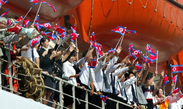 FILE - In this Sept. 5, 2003 file photo, a group of young Northern-alligned Koreans residing in Japan, among passengers cheer and wave the North Korean national flags from the upper deck on North Korean ferry Mangyongbong-92 upon its departure for the communist country at a port in Niigata, northern Japan. Japan approved easing its sanctions on North Korea on Friday in response to Pyongyang's reopening of a probe into the fate of at least a dozen Japanese allegedly abducted to the North decades ago. (AP Photo/Itsuo Inouye, File)