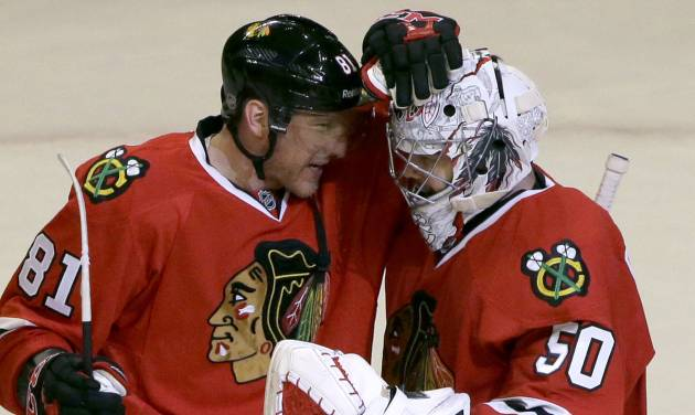 Chicago Blackhawks goalie Corey Crawford, right, celebrates with Marian Hossa after the Blackhawks defeated the Anaheim Ducks 4-2 in an NHL hockey game in Chicago, Friday, Jan. 17, 2014. (AP Photo/Nam Y. Huh)