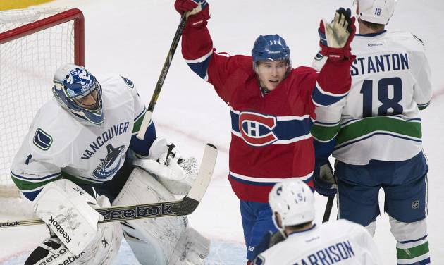 UPDATES WITH CHANGE IN CREDIT FOR GOAL, TO MAX PACIORETTY, INSTEAD OF P.K. SUBBAN - Montreal Canadiens' Brendan Gallagher, center, celebrates a goal by teammate Max Pacioretty against Vancouver Canucks goaltender Roberto Luongo, left, as Canucks' Jason Garrison and Ryan Stanton react during the first period of an NHL hockey game Thursday, Feb. 6, 2014, in Montreal. (AP Photo/The Canadian Press, Graham Hughes)
