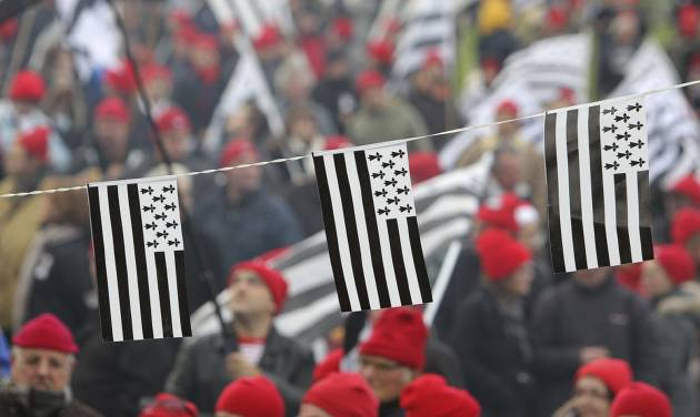 """REMOVES THE REFERENCE TO THE NUMBER OF YEARS OF THE ADMINISTRATIVE REGIONS FILE - In this Nov.30, 2013 file photo, protesters wearing red hats and flags of Brittany take part a demonstration against job losses and against the government's """"eco-tax"""", a controversial environmental tax on heavy good Is vehicles, in Carhaix, Brittany.  France's administrative regions have been part of the identity of citizens of the sprawling and diverse country. Now, merging some of them is seen as a logical way to save money on bureaucracy, and the French support it _ as long as it's someone else's region.  (AP Photo/David Vincent, FILE)"""