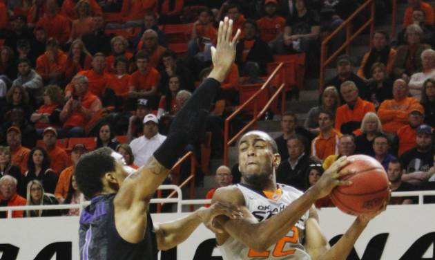 Oklahoma State's Markel Brown (22) attempts to jump by Kansas State defender Shane Southwell, left, during an NCAA college basketball game in Stillwater, Okla., Monday, March 3, 2014. Oklahoma State won 77-61. (AP Photo/The Oklahoman, KT King)