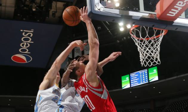 Houston Rockets forward Donatas Motiejunas, third from left, of Lithuania, is fouled as he goes up for a shot by Denver Nuggets guard Aaron Brooks, second from left, and center Timoey Mozgov, of Russia, left, as guard Randy Foye, right, looks on in the first quarter of an NBA basketball game in Denver on Wednesday, April 9, 2014. (AP Photo/David Zalubowski)