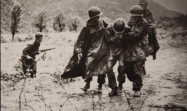 This image provided by the U.S. Army shows U.S. Army chaplain, Capt. Emil J. Kapaun, right, and Capt. Jerome A. Dolan, a medical officer with the 8th Cavalry regiment carrying an exhausted Soldier off a battlefield in Korea, Nov. 1950. President Barack Obama awarded the Medal of Honor Thursday April 11, 2013 to the Army chaplain from Kansas who risked his life dodging gunfire to provide medical and spiritual aid to wounded soldiers before dying in captivity more than 60 years ago during the Korean War. (AP Photo/US Army)