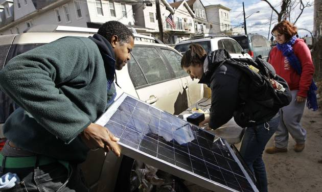 Solar engineers David Gibbs, left, and Arlae Castellanos set up a solar charging station made by Castellanos's high school students on Beach 91st Street in the Rockaways, Saturday, Nov. 3, 2012, in New York. More New Yorkers awoke Saturday to power being restored for the first time since Superstorm Sandy pummeled the region, but patience wore thin among those in the region who have been without power for most of the week. (AP Photo/Kathy Willens)