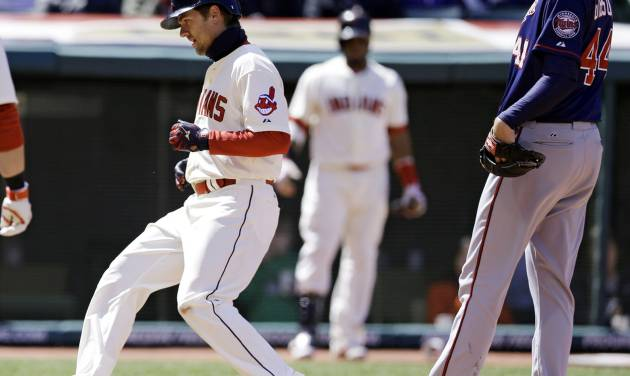 Cleveland Indians' Lonnie Chisenhall, left, scores on a wild pitch by Minnesota Twins starting pitcher Kyle Gibson, right, during the third inning of a baseball game, Saturday, April 5, 2014, in Cleveland. (AP Photo/Tony Dejak)