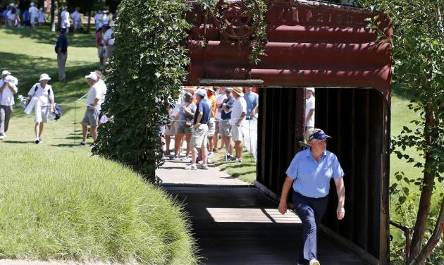 Colin Montgomerie walks through a bridge made out of an old railroad box car during the second round of the U.S. Senior Open golf tournament at Oak Tree National in Edmond, Okla., Friday, July 11, 2014. (AP Photo/Sue Ogrocki)