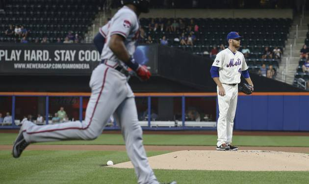 Atlanta Braves' Jason Heyward, left, runs toward home plate after hitting a solo home run off New York Mets starting pitcher Zack Wheeler, right, in the first inning of a baseball game, Wednesday, Aug. 27, 2014, in New York. (AP Photo/John Minchillo)