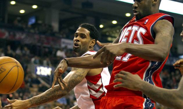 Toronto Raptors' Gary Forbes, back, and New Jersey Nets' Johan Petro battle for the ball as it goes out of bounds during the first half of an NBA basketball game action in Toronto on Thursday, April 26, 2012. (AP Photo/The Canadian Press, Frank Gunn)