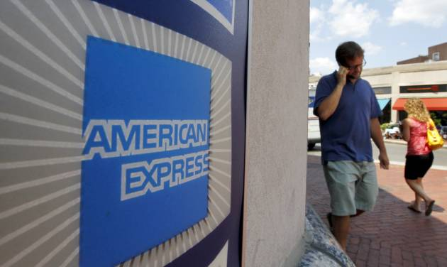 FILE - In this July 19, 2011 file photo, people walk past an American Express logo near the entrance to a bank in the Harvard Square neighborhood of Cambridge, Mass. American Express Co. on Thursday, Jan. 10, 2013 said that it will slash about 5,400 jobs, mainly in its travel business, as it seeks to cut costs and transform its operations as more of its customers shift to online portals for booking travel plans and other needs. (AP Photo/Steven Senne, File)