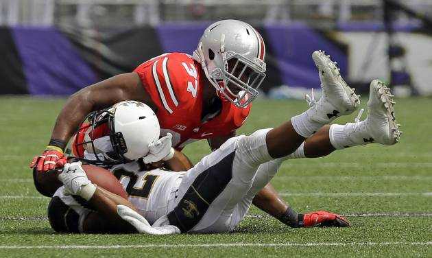 Navy wide receiver Ryan Williams-Jenkins, bottom, loses his helmet as he is tackled by Ohio State linebacker Joshua Perry during the second half of an NCAA college football game in Baltimore, Saturday, Aug. 30, 2014. Ohio State won 34-17. (AP Photo/Patrick Semansky)