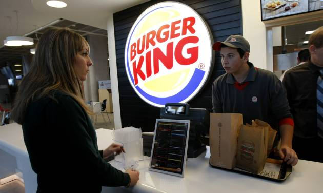FILE - In a Saturday, Dec. 22, 2012 file photo, a customer purchases a meal at a Burger King restaurant in Marseille-Provence airport, in Marignane, France. Burger King is in talks to buy Tim Hortons in hopes of creating a new, publicly traded company with its headquarters in Canada. (AP Photo/Claude Paris, File)