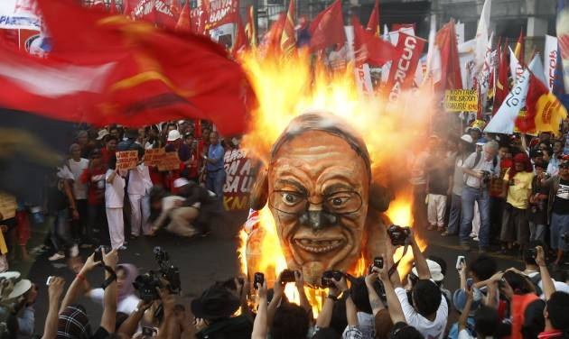 Protesters burn an effigy of Philippine President Benigno Aquino III during a rally near the Presidential Palace in Manila to celebrate international Labor Day known as May Day Tuesday May 1, 2012 in the Philippines. Thousands of workers marched under a brutal sun in Manila to demand a wage increase amid an onslaught of oil price increases, but the Philippine President rejected a $3 daily pay hike which the workers have been demanding since 1999 and warned may worsen inflation, spark layoffs and turn away foreign investors. (AP Photo/Bullit Marquez)