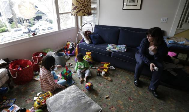 EMBARGOED UNTIL MIDNIGHT EASTERN TIME SUNDAY, FEB. 17 - Nancy Jensen, right, watches as her children, Elizabeth, 6, left, and Joe, 2, center, play with a building set and other toys, Tuesday, Feb. 12, 2013 at their home in Seattle. Nancy was a participant in a new University of Washington study on the effects of television viewing on kids that will be published Monday, Feb. 18, 2013. As a result of what she learned, her children spend more time with hands-on toys and less time watching TV. (AP Photo/Ted S. Warren)