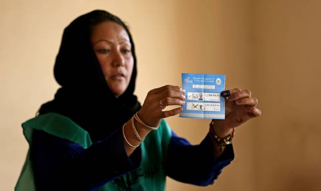 An Independent Election Commission (IEC) employee shows a ballot to observers at a polling station in Kabul, Afghanistan, Saturday, June 14, 2014. Despite a Taliban threat to stay away, Afghans lined up Saturday to vote in a presidential runoff between two candidates who both promise to improve ties with the West and combat corruption as they confront a powerful Taliban insurgency and preside over the withdrawal of most foreign troops by the end of the year. (AP Photo/Massoud Hossaini)