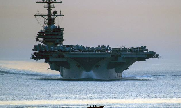 This image provided by the U.S. Navy shows a small vessel transiting in front of the aircraft carrier USS George H.W. Bush as it transits the Strait of Hormuz April 28, 2014 as seen from the guided-missile cruiser USS Philippine Sea. Defense Secretary Chuck Hagel ordered the USS George H.W. Bush from the northern Arabian Sea Saturday June 14, 2014 as President Barack Obama considered possible military options for Iraq. (AP Photo/US Navy, Specialist 3rd Class Abe McNatt)