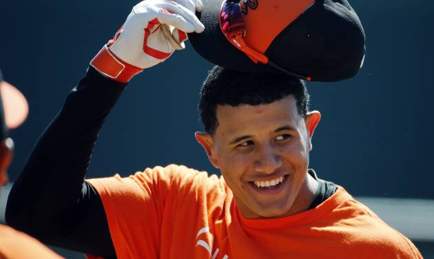 Baltimore Orioles' Manny Machado takes off his hat before going into the batting cage to hit before an exhibition spring training baseball game against the Boston Red Sox in Sarasota, Fla., Saturday, March 8, 2014. (AP Photo/Gene J. Puskar)