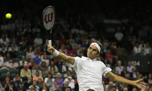 Roger Federer of Switzerland leaps as he plays a return to Gilles Muller of Luxembourg during their men's singles match at the All England Lawn Tennis Championships in Wimbledon, London, Thursday, June 26, 2014. (AP Photo/Pavel Golovkin)