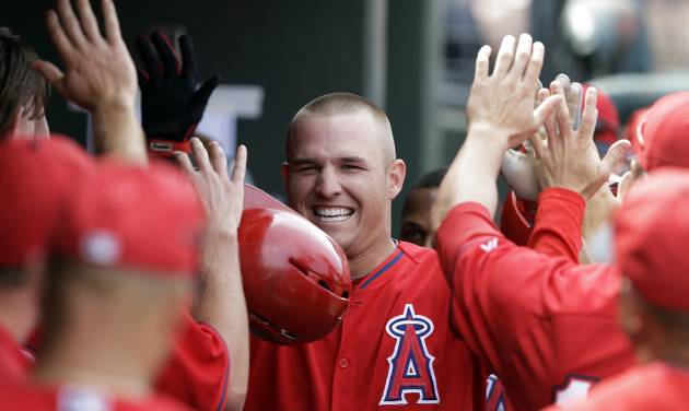 Los Angeles Angels' Mike Trout is congratulated by teammates after hitting a two-run home run during the sixth inning of a spring exhibition baseball game against the Kansas City Royals, Thursday, March 20, 2014, in Surprise, Ariz. (AP Photo/Darron Cummings)